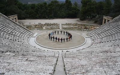 Students stand In a circle at the theater at the Sanctuary of Asclepius at Epidauros.