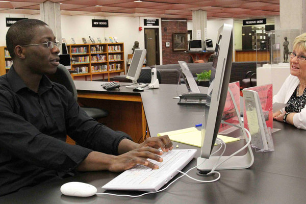 A Help Desk worker helps out a worker with technology problems.