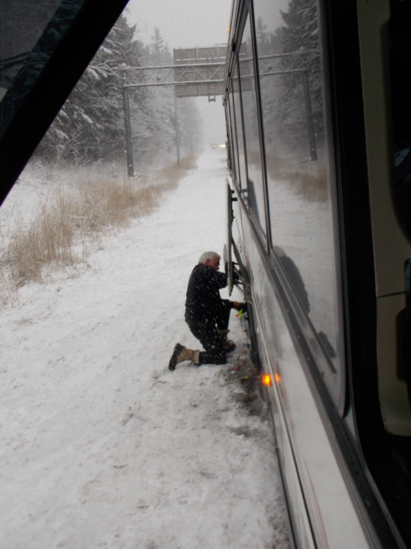 "Heroic bus driver Roy placing chains on the bus's tires.<a href=""/reason/images/594625_orig.jpg"" title=""High res"">∝</a>"