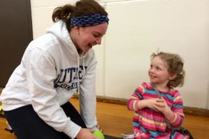 Social work major volunteering with a child from the community.