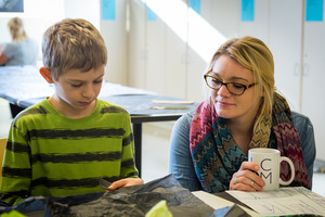 A Luther student works with an elementary school student in an art education classroom.