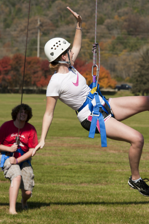 A Luther student is belayed down from the challenge course.