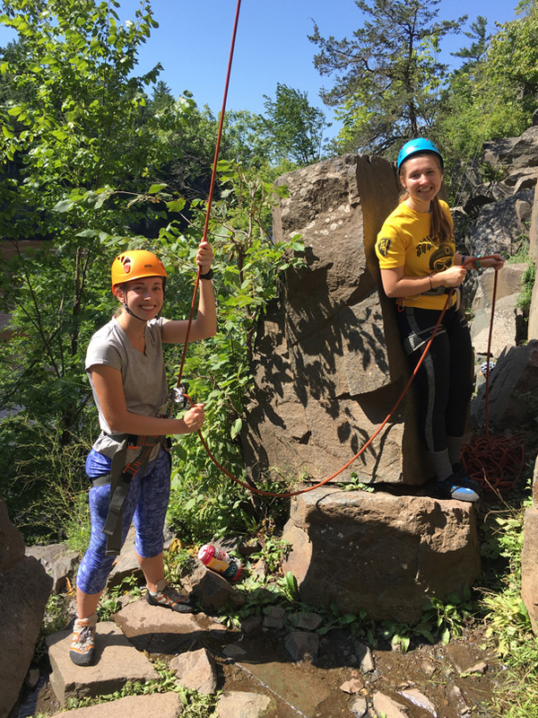 Two students rock climb in the Driftless Area.