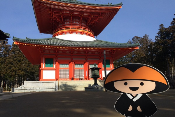 A photo of the cartoon Kukai in front of Konpon Daito (The Great Stupa) on Mount Koya