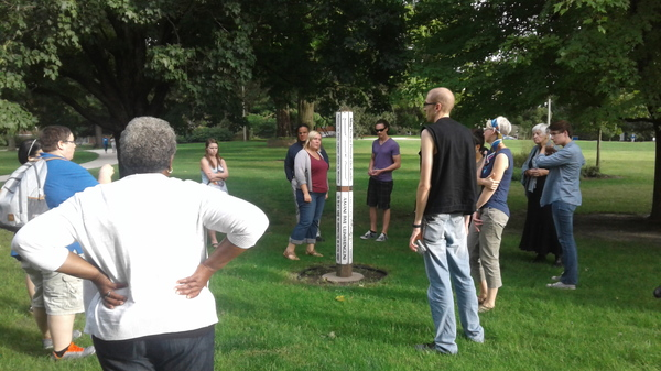 Students and faculty gather around the Peace Pole on their walk for peace.