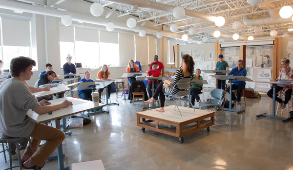 Students sketch a live model in a drawing class.