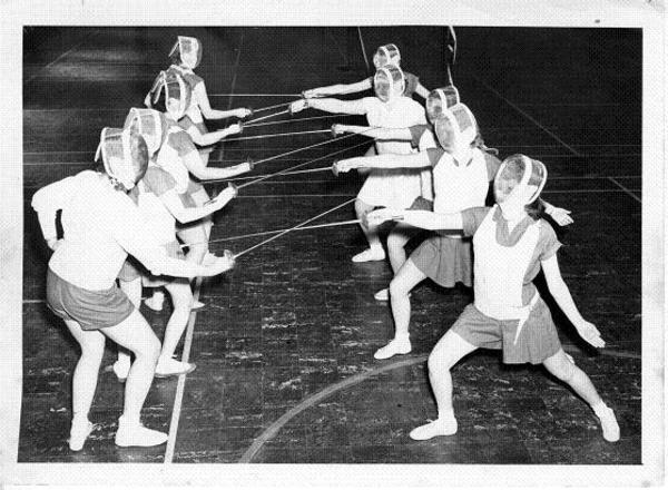 "Fencing was introduced in 1949 by Madeleine Fried, then director of women's physical education. She organized the first fencing clinic in the Midwest, which continued annually. In the December 7, 1951 issue of the Chips, Jane Johnson the fencing chairman stated that the purpose of the fencing clinic was ""to promote interest and further knowledge of foil fencing to this section of the Midwest."" The 1951 clinic included lectures on ""The History of Fencing,"" ""Why Fencing Should Be Included in the Curriculum,"" ""Basic Techniques of Fencing,"" and ""Care and Selection of Equipment."" Speakers from the University of Illinois and the Fencer's Club of Chicago were also part of the 1951 program. The 1952 clinic included delegations from Grinnell College, Gustavus Adolphus College, La Crosse State College, Waldorf Junior College, the state universities of Wisconsin, Illinois, and Iowa, and even high schools from Anamosa, Elkader, Zumbrota, and Decorah.<a href=""/reason/images/469762_orig.jpg"" title=""High res"">∝</a>"