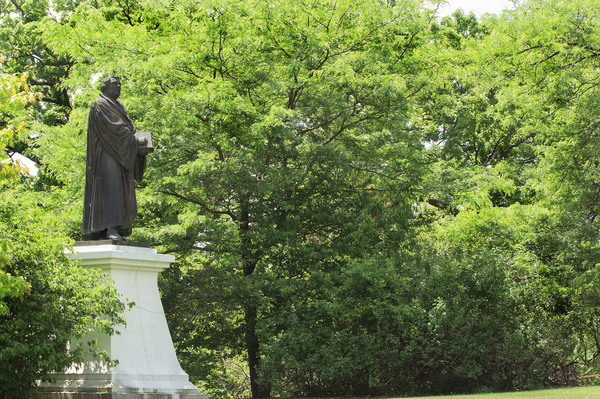 Statue of Martin Luther nestled in the trees on Luther College Campus
