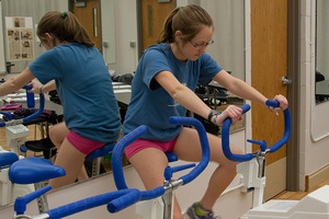A student peddling a workout bike in a Physiology of Exercise Lab.