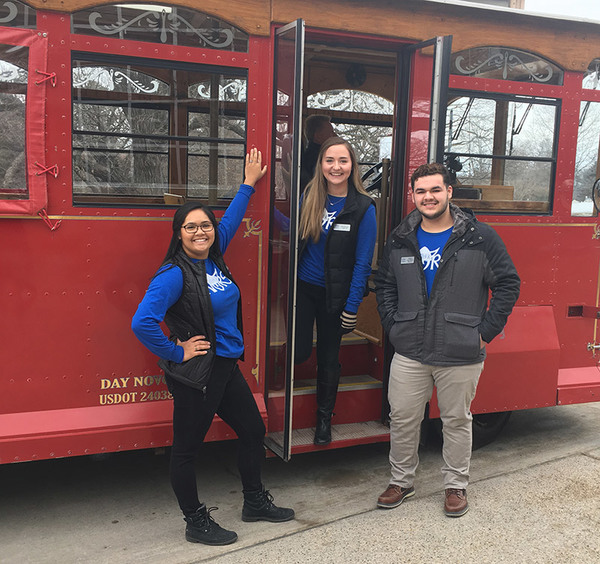 Students posing in front of a trolley, which is used for tours around Decorah during the visit.