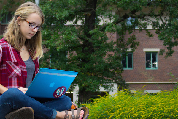Student sitting with laptop in front of Olin building.