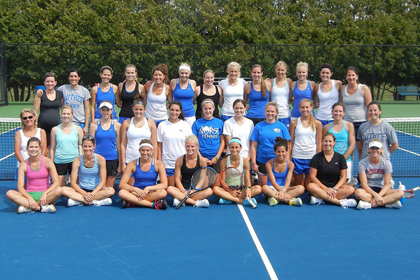 A large group of Luther tennis alumni pose for a photo on the tennis court.