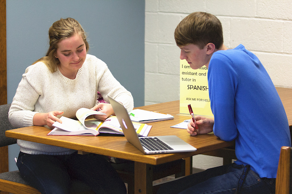 A trained student tutor assists a student.