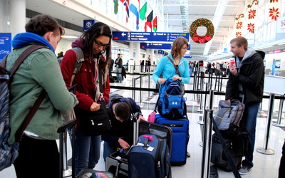 Sadie Stoiber, Maggie Steinberg, Julia Joseph, and Andrew Sharot grab their passports from their bags before checking their suitcases.