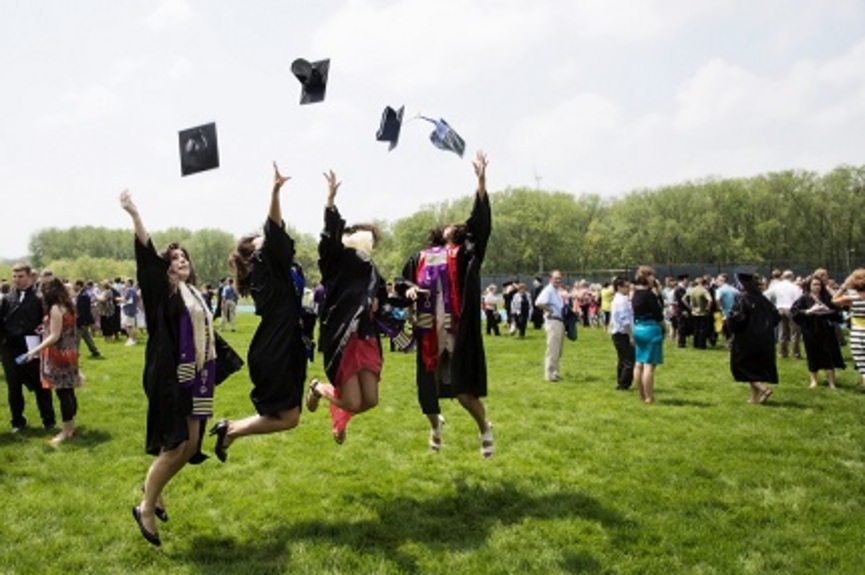 Recent graduates wearing their gowns celebrate by throwing their caps into the air while jumping.