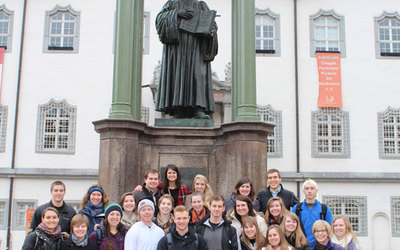 Photo of the group in front of a statue of Martin Luther.