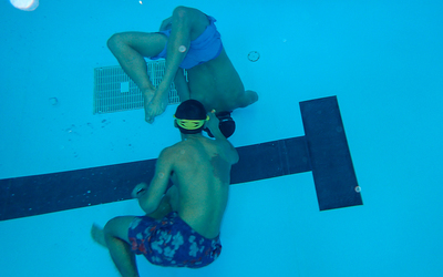 Students practice snorkeling in the Luther pool by retrieving diving toys.