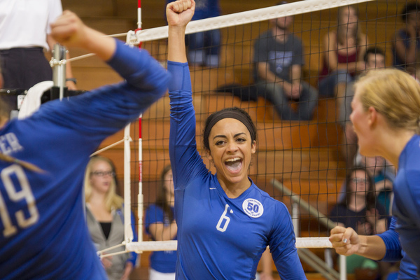 A volleyball player celebrating victory after a win.