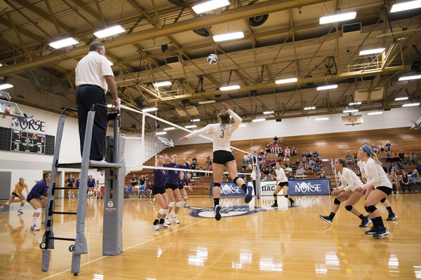 The volleyball team playing at home in the main gym.