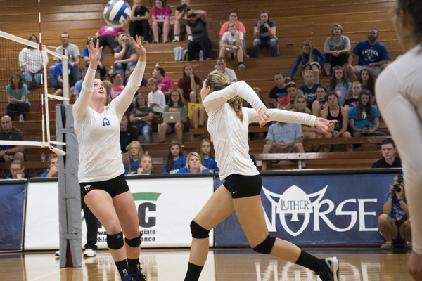 Luther volleyball team setting and striking the ball to the opponents.