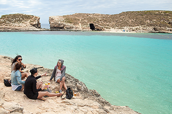 Luther students sit by the ocean while studying in Malta.