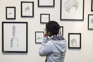 A Luther student views drawings in a gallery.