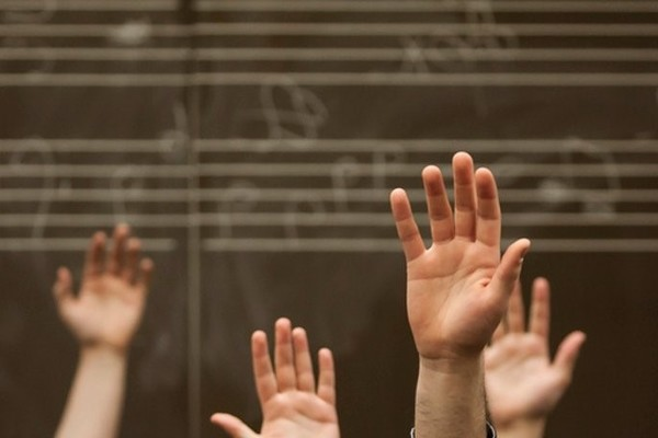 Music students with their hands raised